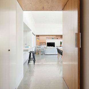 Aménagement d'un couloir contemporain avec béton au sol et un sol gris.