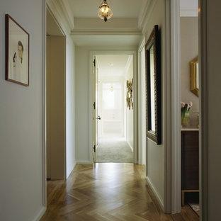 Elegant medium tone wood floor hallway photo in New York with beige walls