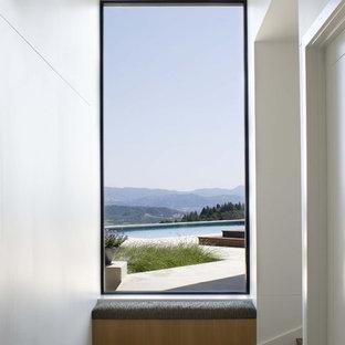 Aménagement d'un couloir moderne avec un mur blanc et un sol en bois brun.