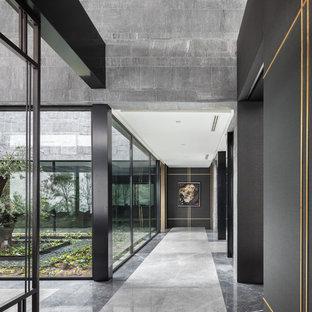 コンテンポラリースタイルのおしゃれな廊下 (黒い壁、グレーの床) の写真