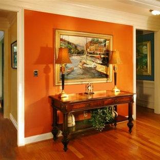 Immagine di un ingresso o corridoio chic di medie dimensioni con pavimento arancione, pareti arancioni e pavimento in legno massello medio