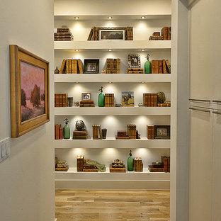 Diseño de recibidores y pasillos contemporáneos con paredes blancas y suelo de madera en tonos medios