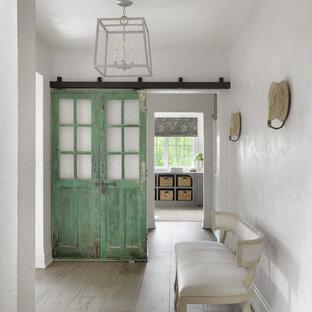 Inspiration pour un couloir rustique avec un mur blanc, un sol en bois clair et un sol gris.