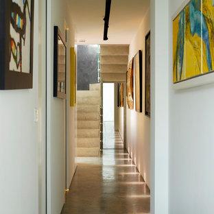 Idéer för en mycket stor modern hall, med gula väggar, betonggolv och grått golv