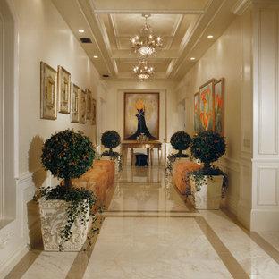 Réalisation d'un très grand couloir tradition avec un mur blanc, un sol en marbre et un sol beige.