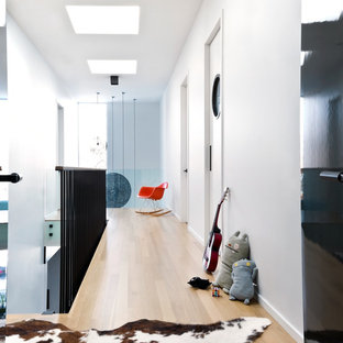 Example of a danish light wood floor hallway design in Chicago with white walls