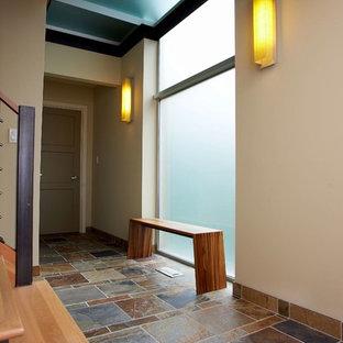 Cette image montre un couloir design de taille moyenne avec un mur beige, un sol en ardoise, un sol multicolore et un plafond en poutres apparentes.