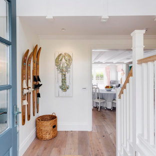 Photo of a large beach style hallway in Devon with white walls, medium hardwood floors and brown floor.