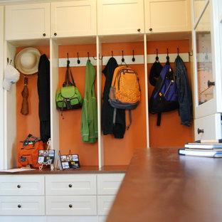 Cette image montre un couloir traditionnel de taille moyenne avec un mur orange et un sol en bois foncé.