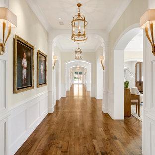Idéer för att renovera en stor hall, med vita väggar, mellanmörkt trägolv och brunt golv