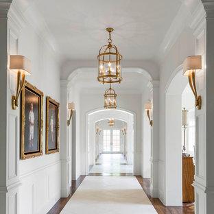 Idée de décoration pour un grand couloir tradition avec un mur blanc et un sol en travertin.