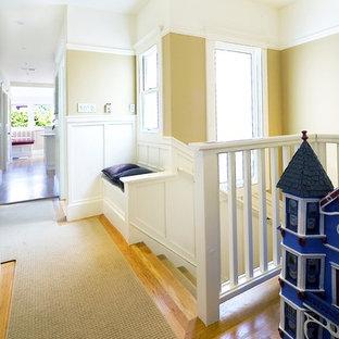 Exemple d'un couloir chic avec un mur beige, un sol en bois brun et un sol jaune.