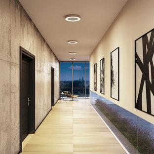 Large trendy light wood floor and beige floor hallway photo with beige walls