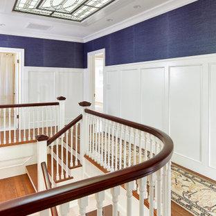 Réalisation d'un couloir tradition avec un mur bleu, un sol en bois brun, un sol marron, boiseries et du papier peint.