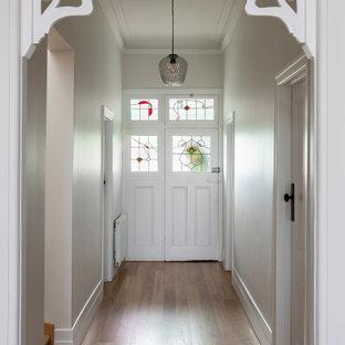 Exempel på en stor modern hall, med vita väggar, mellanmörkt trägolv och brunt golv