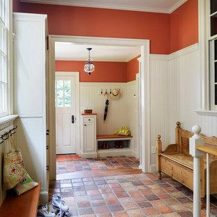 Esempio di un ingresso o corridoio chic con pareti arancioni, pavimento in terracotta e pavimento arancione