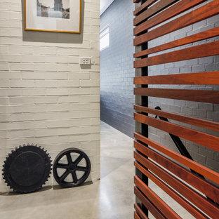 Exemple d'un couloir tendance de taille moyenne avec un mur blanc, béton au sol, un sol gris et un mur en parement de brique.