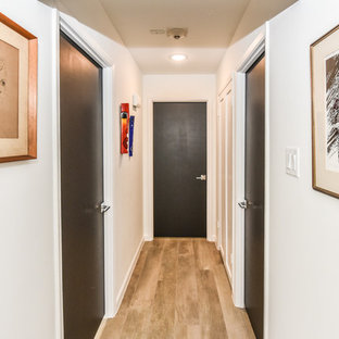 Design ideas for a mid-sized midcentury hallway in Houston with white walls, porcelain floors and beige floor.