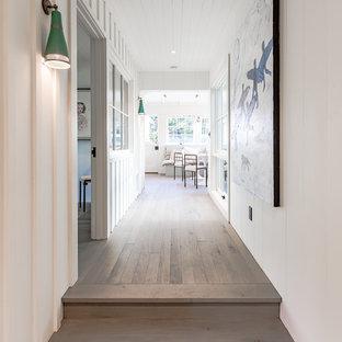 Mid-sized beach style hallway in Santa Barbara with white walls, medium hardwood floors and brown floor.