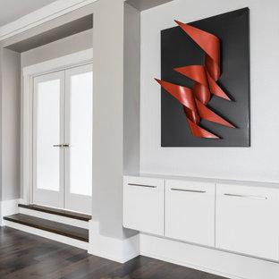 Aménagement d'un grand couloir contemporain avec un mur gris, un sol en bois foncé, un sol marron et du papier peint.