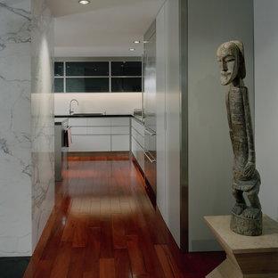 Inspiration pour un couloir design avec un mur blanc et un sol en bois brun.