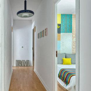 Cette photo montre un couloir tendance de taille moyenne avec un mur blanc et un sol en bois clair.