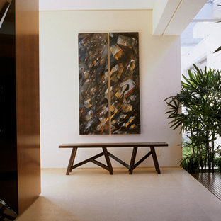 Inspiration for a large contemporary limestone floor and beige floor hallway remodel in Miami with beige walls