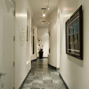 Aménagement d'un couloir contemporain avec un mur blanc et un sol gris.