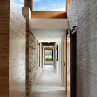 Cette photo montre un très grand couloir tendance en bois avec un mur multicolore, un sol gris et un plafond en bois.