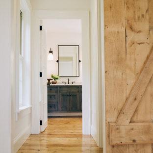 Inspiration för en mellanstor lantlig hall, med vita väggar och ljust trägolv
