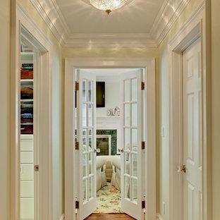 Aménagement d'un grand couloir classique avec un mur vert et un sol en bois brun.