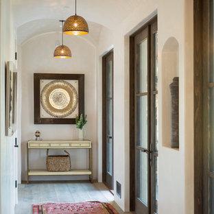 Medelhavsstil inredning av en mellanstor hall, med beige väggar, ljust trägolv och beiget golv