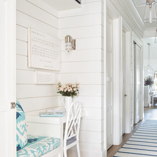 Example of a beach style medium tone wood floor and brown floor hallway design in Miami with white walls