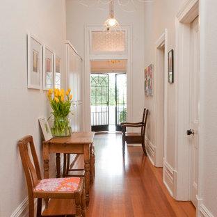 パースのエクレクティックスタイルのおしゃれな廊下 (白い壁、無垢フローリング、オレンジの床) の写真