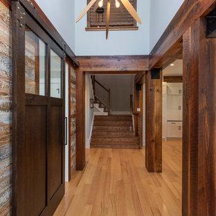 Idée de décoration pour un grand couloir champêtre en bois avec un mur bleu et un sol noir.