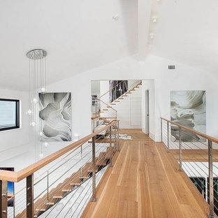 ニューヨークのカントリー風おしゃれな廊下 (白い壁、淡色無垢フローリング、三角天井) の写真