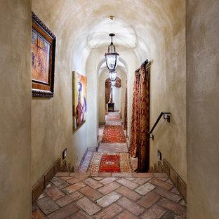 Пример оригинального дизайна интерьера: большой коридор в средиземноморском стиле с бежевыми стенами и кирпичным полом