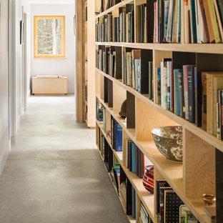 Idée de décoration pour un couloir design de taille moyenne avec un mur blanc et béton au sol.