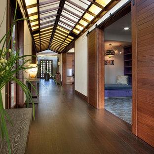 На фото: большой коридор в восточном стиле с белыми стенами, темным паркетным полом и коричневым полом с