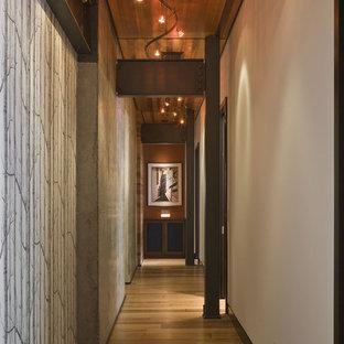 Modern inredning av en hall, med vita väggar och mellanmörkt trägolv