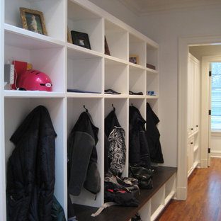 This is an example of a traditional hallway in Chicago with white walls and dark hardwood floors.