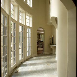 Huge elegant limestone floor hallway photo in Chicago with beige walls