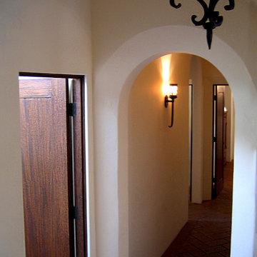 Custom Arch way and Herringbone clay flooring in small Spanish Bungalow