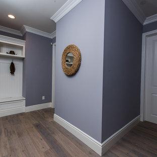 Exempel på en mellanstor modern hall, med lila väggar och mörkt trägolv