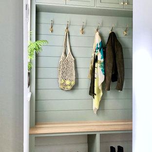 Kleiner Moderner Flur mit grüner Wandfarbe, Laminat, beigem Boden, gewölbter Decke und Holzdielenwänden in Sonstige