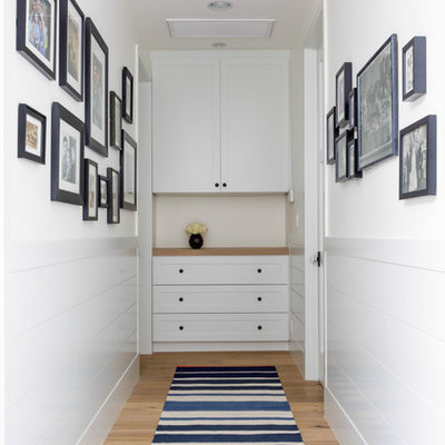 Transitional medium tone wood floor hallway photo in Los Angeles with white walls