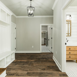 Example of a huge farmhouse porcelain floor and brown floor hallway design in Houston with beige walls