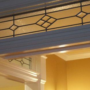 ニューヨークの広いトラディショナルスタイルのおしゃれな廊下 (黄色い壁、無垢フローリング、茶色い床) の写真