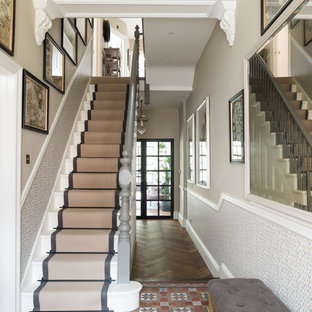 This is an example of a large transitional hallway in London with beige walls, porcelain floors and multi-coloured floor.