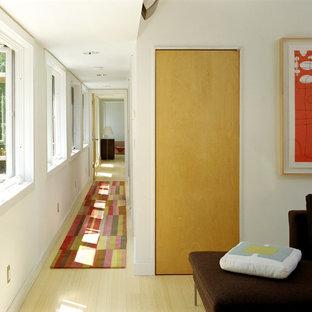 Bild på en funkis hall, med ljust trägolv och vita väggar